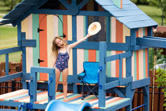 Celebrating child waving hat on outdoor playset. Celebrating child waving hat on newly painted outdoor recreation playground with slide, handlebars, chair, door Royalty Free Stock Photo