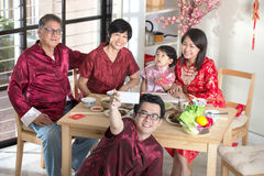 Celebrating Chinese New Year. Reunion dinner. Happy Asian Chinese multi generation family with red cheongsam selfie while dining at home