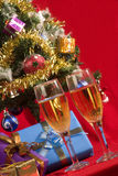 CELEBRATING CHRISTMAS. Two glasses with wine  and gifts with christmas tree as background Stock Images