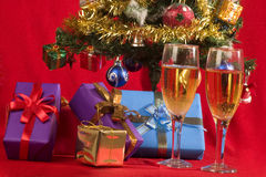 CELEBRATING CHRISTMAS. Two glasses with wine  and gifts with christmas tree as background Royalty Free Stock Photography