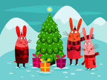 Celebrating Christmas. Illustration of three funny rabbits standing in awe in front of a Christmas tree Royalty Free Stock Image