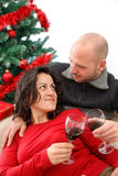 Celebrating Christmas. Young couple at sofa celebrating Christmas with a cup of wine Stock Photography
