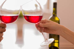 Celebrating by clinking glasses of red wine. Tall stemmed wine glasses to celebrate on a romantic date Stock Images