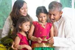 Celebrating diwali. Indian family in traditional sari celebrate diwali or deepavali at home, little girl hands holding oil lamp with father indoor stock photography
