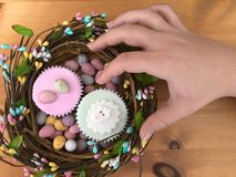 Woman`s hand reaching for an Easter cupcake stock images