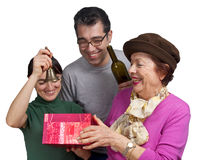 Celebrating Family. A family with mother , daughter and son celebrating a seasonal holiday with a gift box and a bottle of wine, isolated on white Royalty Free Stock Photography