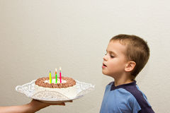Celebrating fifth birthday boy cake son blowing candle Stock Image