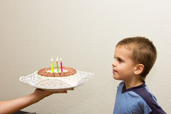 Celebrating fifth birthday boy cake son blowing candle Royalty Free Stock Photography