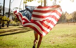 Celebrating fourth of july in the park. Rear view of young woman running in the forest with American Flag. American girl celebrating fourth of july in the park stock photography