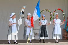 Women of the French community in national costume with flag. Celebrating French culture at a multicultural festival with traditional dress, a French tricolor stock photos
