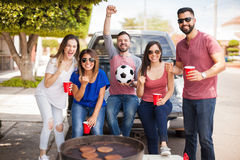 Celebrating a goal and watching soccer game. Group of young Hispanic friends celebrating their team score a goal while tailgating at a game and grilling burgers royalty free stock photography