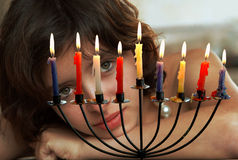 Celebrating Hanukkah. Special candleholder for Hanukkah ,with 8 candles and a pretty young girl looking at them Stock Photography
