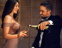 Celebrating a happy laughing couple with a glass of champagne Royalty Free Stock Images