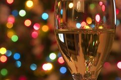 Celebrating the Holidays. Close up on a Wine Glass with the Christmas lights on the background Stock Photos