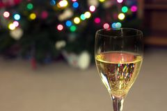 Celebrating the Holidays. Close up on a Wine Glass with the Christmas lights on the background Royalty Free Stock Photography