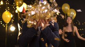 Celebrating man blowing holiday confetti on camera, dancing people on background. Stock footage stock footage