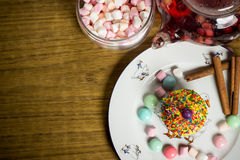 Celebrating marshmallow, cake, candies, fruit tea on wooden table, birthday Stock Image