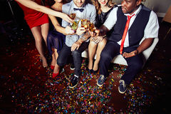 Celebrating Momentous Event at Night Club. High angle view of unrecognizable group of friends toasting with champagne flutes while celebrating momentous event at stock photography