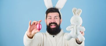 Celebrating the new life. Hipster with long rabbit ears holding egg laying hare. Bearded man with bunny toy and Easter. Egg. Celebration of spring time holiday royalty free stock image