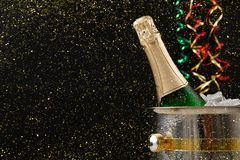 Bottle of champagne in a bucket on dark backgroud. Copy space Royalty Free Stock Photography