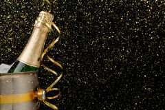 Decorated bottle of champagne in a bucket on dark backgroud. Copy space Stock Image