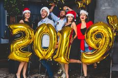 Celebrating New Year party. Group of cheerful young girls in beautiful wearing carrying gold colored numbers 2019 and royalty free stock photo