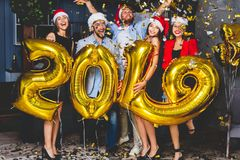 Celebrating New Year party. Group of cheerful young girls in beautiful wearing carrying gold colored numbers 2019 and stock image