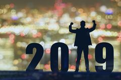 Celebrating new year 2019 Silhouette freedom young hope business man standing and enjoying on the the top of the building, city sc. Ape, landscape and 2019 years stock photos