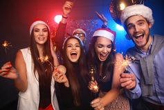 Celebrating New Year together. Group of beautiful young people in Santa hats throwing colorful confetti, looking happy Stock Photos