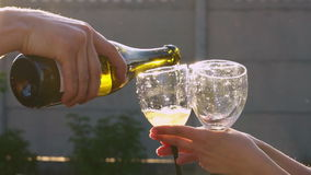 Celebrating at the open air. Man opening a bottle of champagne. Woman holding two glasses. Sparkling wine poured into wineglass. Unrecognizable people celebrate stock video