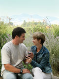 Celebrating outdoors. Young couple having picnic with wine Stock Photos
