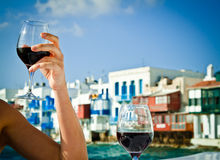 Celebrating by the sea. Celebrating the summer with a glass of wine in Little Venice, Mykonos, Greece Stock Photo