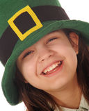 Celebrating St. Patrick's Day. Close-up of a laughing preteen girl celebrating St. Patrick's Day in an oversized green hat.  Isolated on white Stock Image