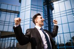 Celebrating success. Excited young businessman keeping arms raised and expressing positive while standing outdoors with office bui. Celebrating success. Low Stock Images
