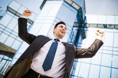 Celebrating success. Excited young businessman keeping arms raised and expressing positive while standing outdoors with office bui. Celebrating success. Low Stock Photography