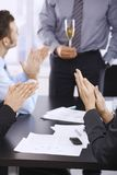 Celebrating success in office. Businesspeople celebrating success with champagne in office, clapping hands. Focus on hand in front Stock Photo