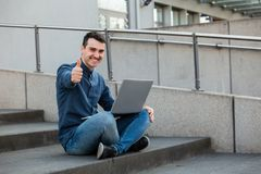 Celebrating success. Smiling happy man with thumb up gesture and  laptop on knees, seated on a stairs celebrating success. Freelancer guy with thumb up working royalty free stock image