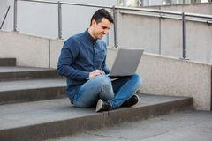 Celebrating success. Smiling male student with laptop on knees, seated on a stairs raising hands up as celebrating success. Concerned freelancer guy working at royalty free stock photography