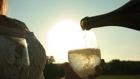 Celebrating success and victory. pour sparkling wine from bottle into transparent wine glasses against a sunset. Celebrating success and victory. pour sparkling stock video footage