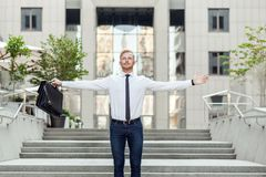 Young adult red hair and bearded businessman keeping arms raised and expressing positivity while standing outdoors with office bui. Celebrating success. Young royalty free stock image