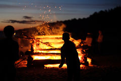Celebrating the summer solstice. Silhouettes of children against the background of a large fire at the celebration of the summer solstice. Latvia stock images