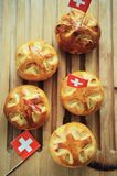 Celebrating Switzerland National Day on August 1st with traditional symbols like swiss flag red with white cross. Special bread b. Uns with cross shape cut royalty free stock image