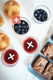 Celebrating Switzerland National Day on August 1st with traditional symbols like swiss flag red with white cross. Special bread b. Uns with cross shape cut. Red royalty free stock photography