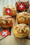 Celebrating Switzerland National Day on August 1st with traditional symbols like swiss flag red with white cross. Special bread b. Uns with cross shape cut stock image