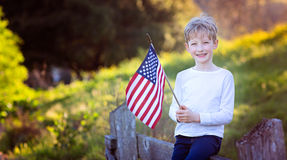 Celebrating 4th of july. Cheerful smiling little boy holding american flag celebrating 4th of july Royalty Free Stock Images