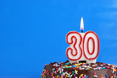 Celebrating Thirty Years. A number candle is lit in celebration of thirty years royalty free stock photos