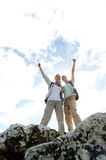Celebrating trek. Successful and happy hiking women on top of a rock stock photo