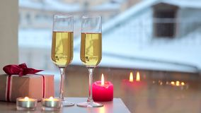 Celebrating Valentine's Day: Gifts and champagne by candlelight. View of the snowy roofs stock video footage