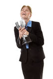 Celebrating a win. Business woman  wearing a suit with a blue shirt, is clutching hold of a trophy to celebrate her win Stock Images