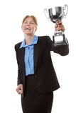 Celebrating a win. Business woman  wearing a suit with a blue shirt, is clutching hold of a trophy to celebrate her win Stock Photos